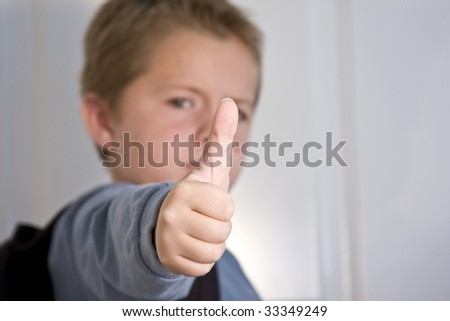 Young boy giving thumbs up with focus on thumb