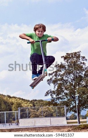 young boy going airborne with his scooter at the skate park