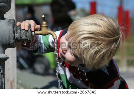 Young  boy gulping down water from a tap