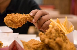 Young Boy hand hold fried chicken for eat , with fast food concept and diet