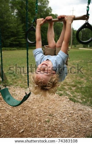 Young Boy Hanging Up Side Down on a Swing Set