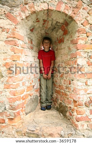 young boy hiding in arch of wall