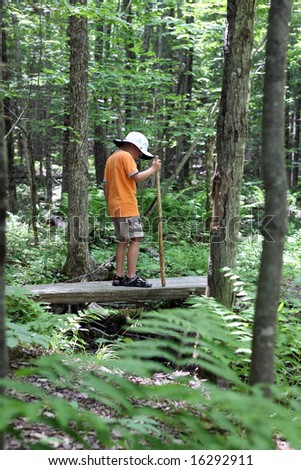 young boy hiking across a small wood bridge