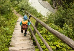young boy hiking on the wooden stairs over wild mountain river in austrian alps near krimm in salzburg