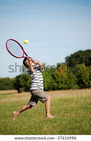 Young boy hitting a tennis ball