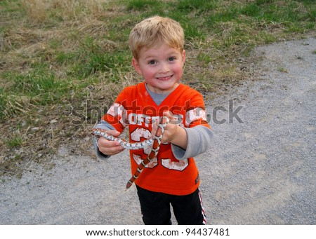 Young boy holding a coral snake mimic, Red Milk Snake, Lampropeltis triangulum syspila