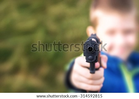 Young boy,holding a toy gun,against green grass background.