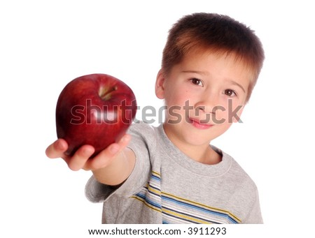 Young Boy Holding an Apple out to give his Teacher.  Focus in on the Boy.