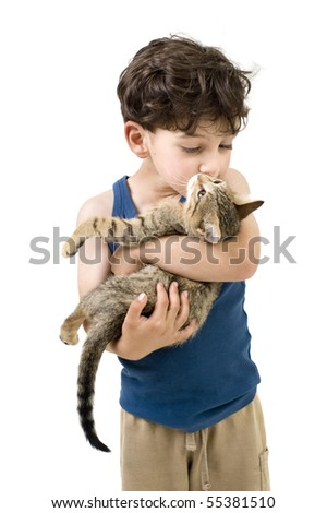 young boy holding and kissing a kitten