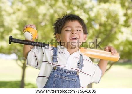 Young boy holding baseball bat outdoors smiling