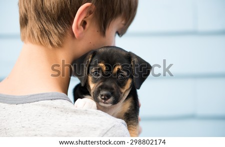 Young Boy Holding Black and Brown Puppy with Floppy Ears