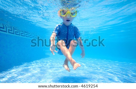 Young boy holding breath underwater in sunny swimming pool on vacation
