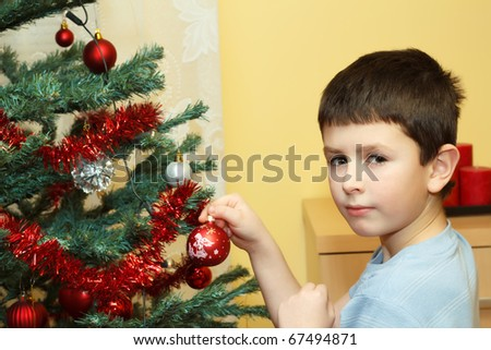 Young boy holding Christmas decorations on tree