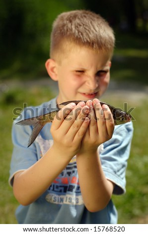 Young boy holding fish he catch