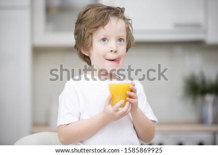 Young boy holding glass of orange juice, licking lips
