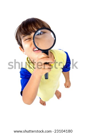 Young boy holding magnifying glass .