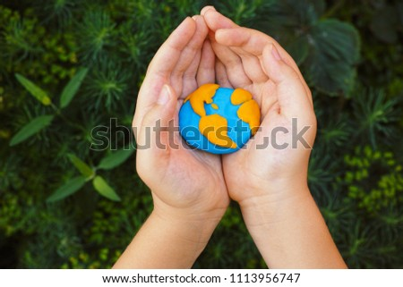 Young boy holding planet Earth in his hands. Concept image. #1113956747