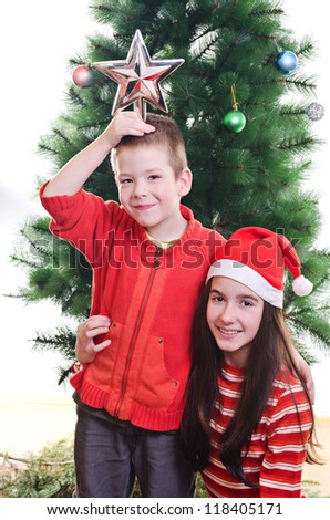 Young boy holding star on top of his head and sister wearing santa hat in front of christmas tree, portrait, looking at camera, vertical shot