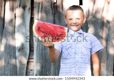 young boy holds a large piece of watermelon against a wooden rural wall, a little schoolboy offers a fresh watermelon on a sunny summer day, free space #1504942343