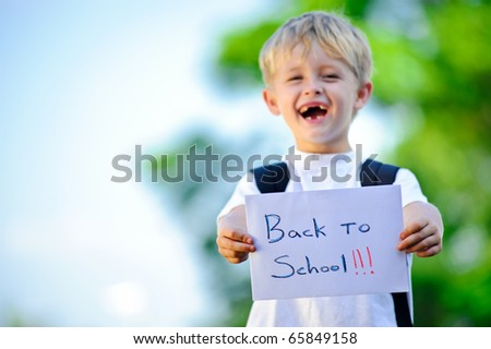 "Young boy holds up handwritten sign ""Back to school!"""