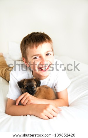 Young Boy Hugging and Playing with Small Fluffy Puppy
