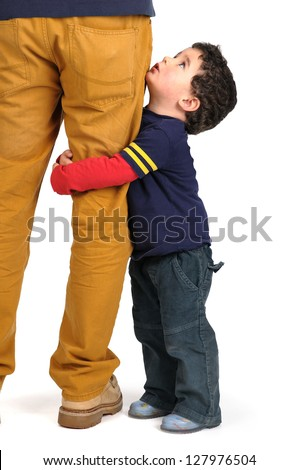 Young boy hugging his father's leg