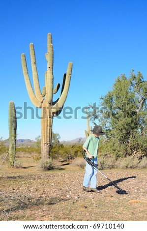 Young boy hunting for treasure with a metal detector