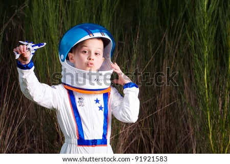 Young boy in an astronaut suit playing with a toy airplane.