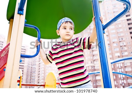 Young boy in bandana on playground thoughtfully looking into the distance against blured apartment blocks
