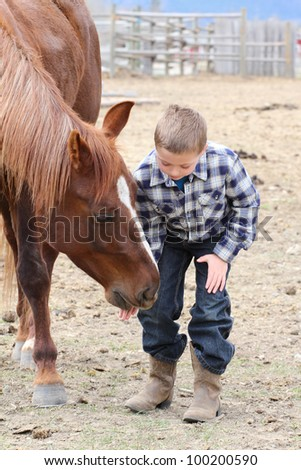 Young boy in blue feeding his horse treats
