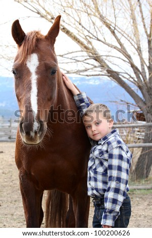 Young boy in blue leaning against his horse