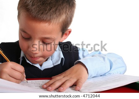 Young boy in elementary/primary school uniform working. Isolated. Copyspace