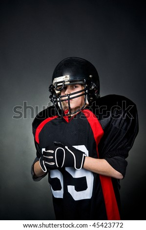 Young boy in football uniform isolated on black