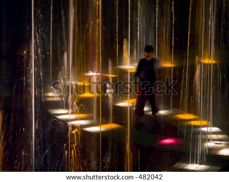 young boy in fountain at night