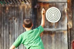Young boy in green t-shirt playing darts outdoor