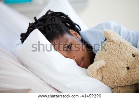 Young Boy in Hospital  hugging his teddy bear - stock photo