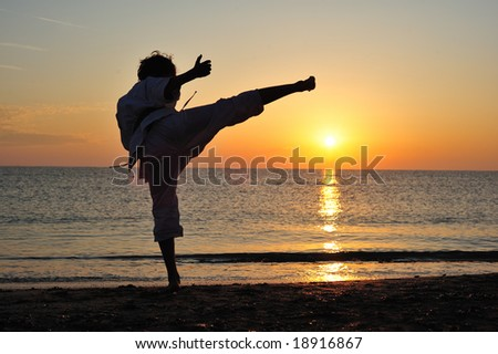 Young boy in karate uniform training at sunset