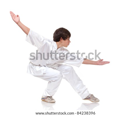 Young boy in kimono practising martial arts on the white background