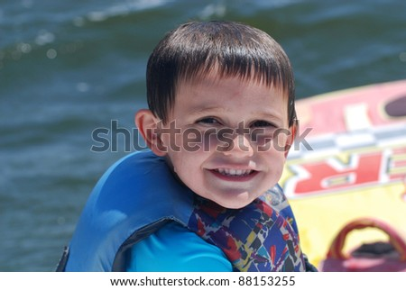 young boy in life jacket on lake