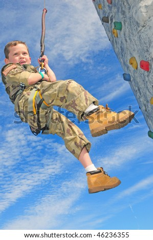 Young boy in military clothes practicing rappelling