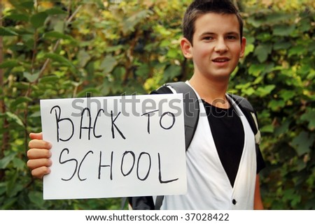 young boy in nature holding sign