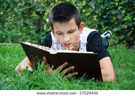 young boy in nature studying