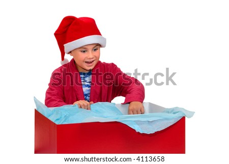 Young boy, in robe and Santa hat, opening a big red gift box, isolated on white with clipping path