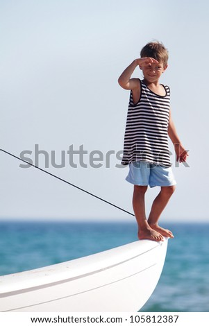 young boy in sailor shirt on board of sea yacht