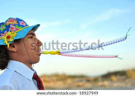 Young boy in shirt and tie blowing in blowers