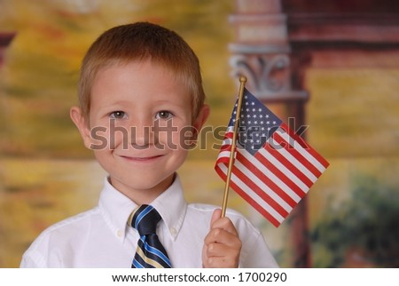 Young boy in tie holding American flag