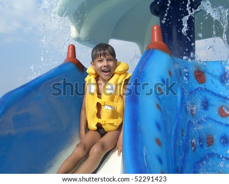 Young boy in yellow life jacket sitting on colorful water slide in aquapark