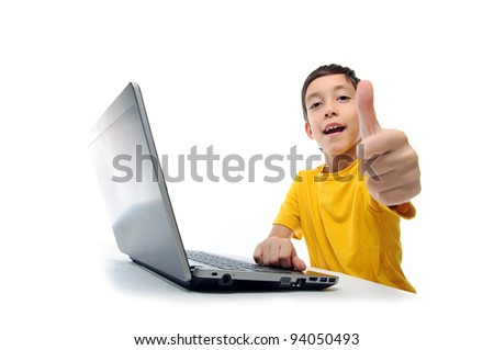young boy in yellow t-shirt with laptop showing thumbs up at camera isolated on white background
