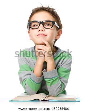 Young boy is daydreaming while reading book and wearing glasses, isolated over white