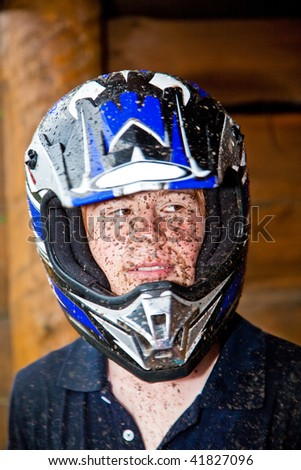 young boy is fascinated by quad driving and enjoys is, his face is dirty from mud